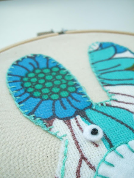 example of tiny blanket stitches used to applique a vintage fabric bunny onto calico fabric