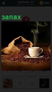 Рассыпанный мешок с кофейными зернами и рядом стоит чашка с кофе из которой идет запах ароматный