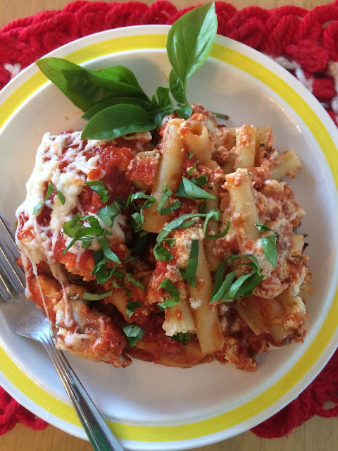 Finished photo of a serving of eggplant baked ziti topped with fresh basil.