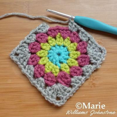 4 rounds of crochet in blue, green, pink and gray