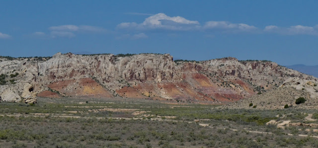 Painted hills of white, orange and red orange; sagebrush-studded flatland foreground blue skies with wispy cloulds above