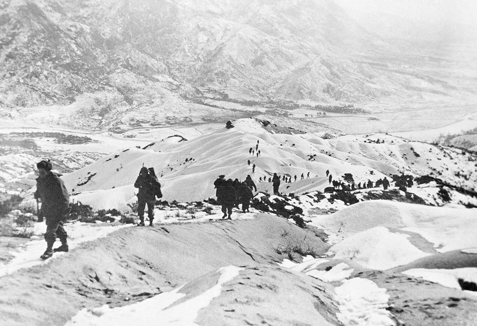 American GIs thread their way over snow-covered hills North of Seoul, South Korean capital on January 14, 1951, during earlier stages of U.N. withdrawal.