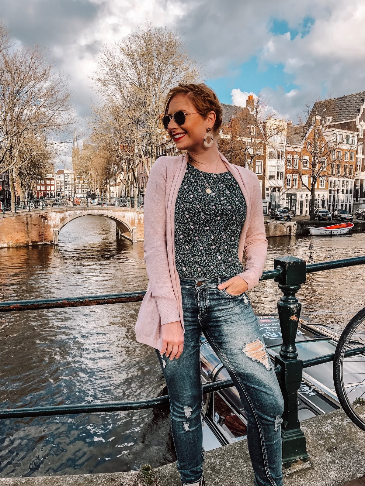 affordable by amanda travel guide to amsterdam, the netherlands. she is wearing a purple cardigan from loft and a loft ditsy top from loft with a pair of distressed denim jeans.