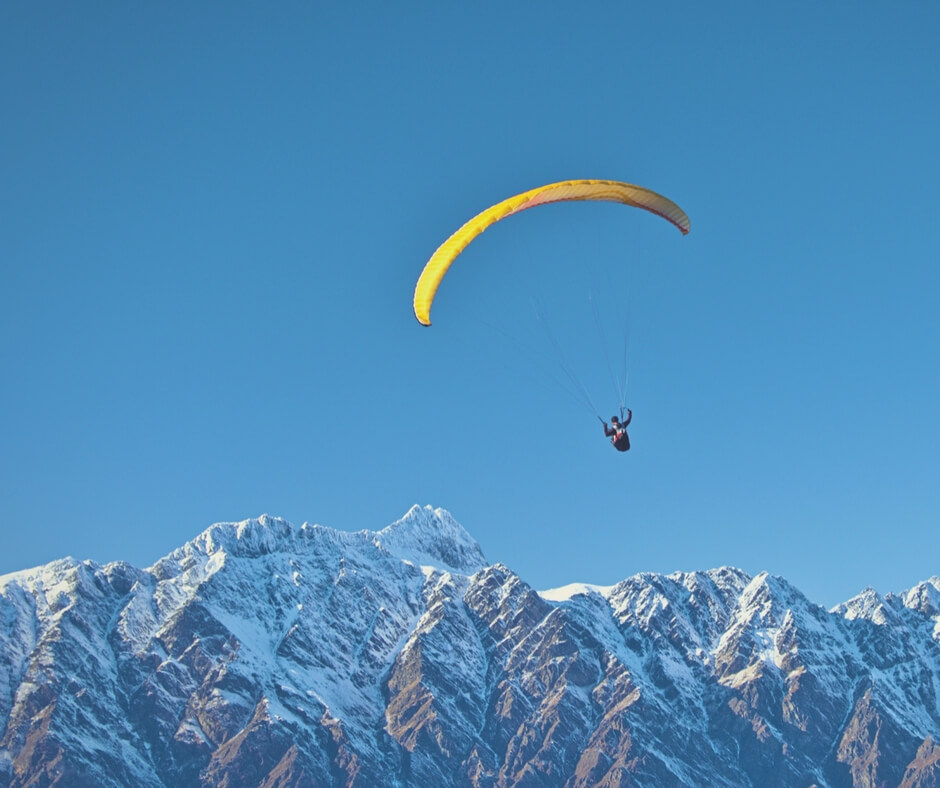 A man hang gliding in a clear blue sky above snow capped mountains.