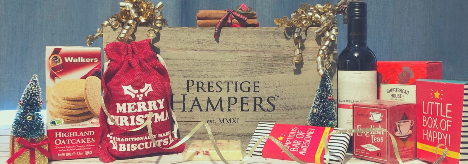 Prestige hampers vintage wooden box containing cookies, biscuits, a bottle of red wine, and tea bags.
