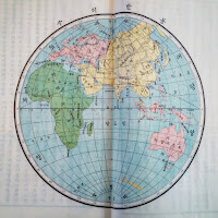 Circle-shaped atlas of the Earth in a white background. The oceans are in sky blue color, African continent in green, Asia in yellow, Europe and Australia in pink.
