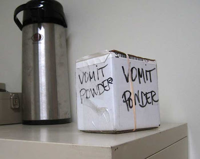 Photo of a smallish cardboard box hand labeled VOMIT POWDER