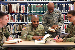 students in uniform sit around a table in the library looking at a book
