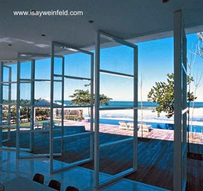 Vista desde la sala de la casa hacia la piscina exterior y el mar