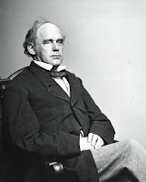 A photograph of Salmon P. Chase seated looking off to the right with his hands folded in his lap and his legs crossed.