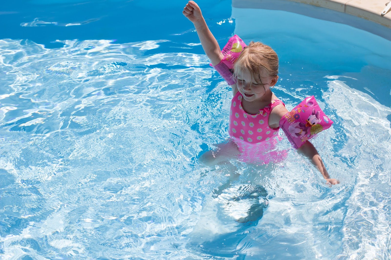 A nearly 5 year old splashing in a swimming pool in a pink swimming costume and arm bands