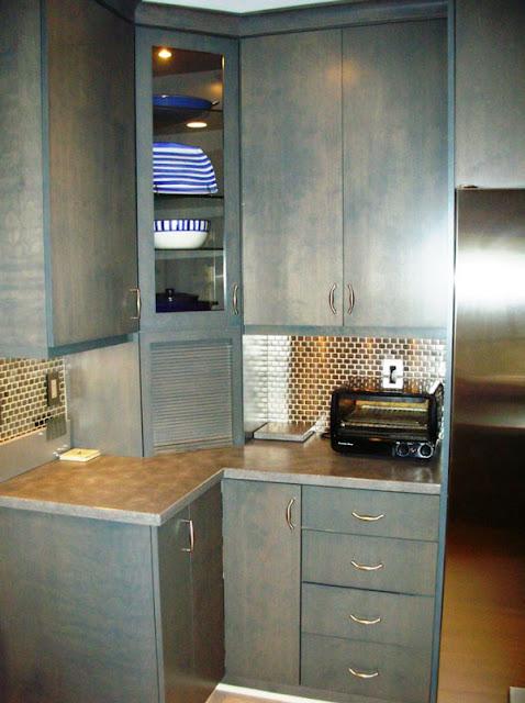 زاوية المطبخ المربعة من الأسفل يعلوها دولاب ذو باب زجاجي شفاف