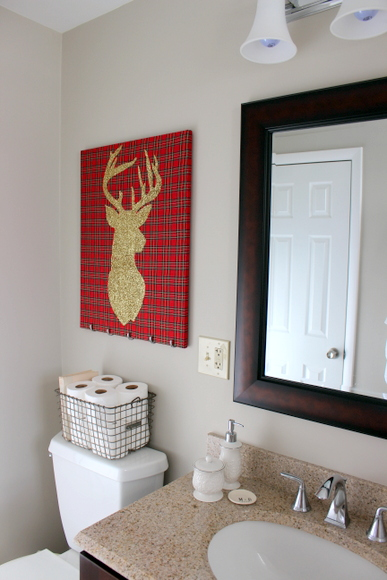 This gold glitter reindeer wall art adds whimsy to this bathroom.