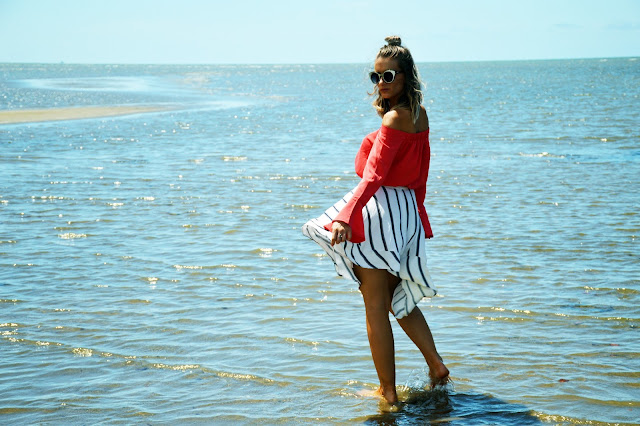 girl on beach summer style flare off shoulder coral top with assymetric stripe skirt