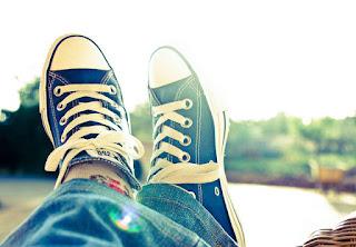 Feet in sneakers relaxing by lake