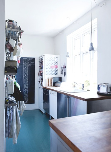 Danish kitchen with stainless appliances, blue floor and silver pendant lights