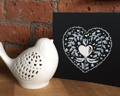Black card hand painted with a Valentines inspired folk art design using a monochromatic palette.  Pictured against a brick wall with a porcelain bird
