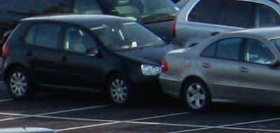 Två bilar bredvid varandra på parkeringsplats.