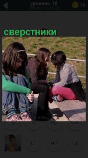 на лавочки сидят несколько подростков, сверстники гуляют на улице