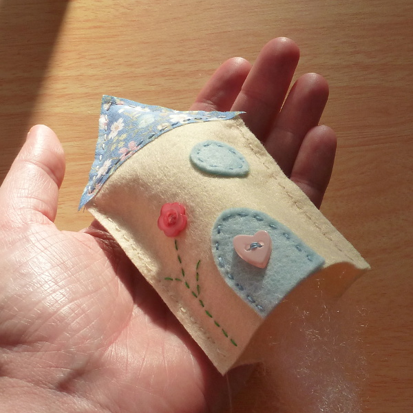 Adding polyester toy filling into the hand sewn plush house