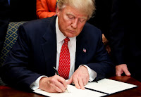 Trump signs document (Credit: Photograph Pool | Getty) Click to Enlarge.