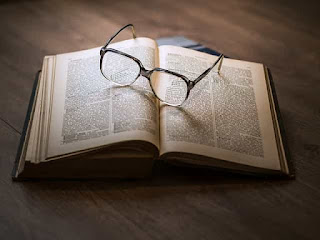 an open book with reading glasses