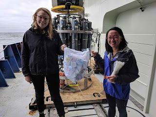 Two women hold a bag full of styfofoam cups. Behind them is the CTD, a gray, oceanographic instrument that has many bottles, each of which close at different depths in the ocean. Behind the instrument is the ocean.