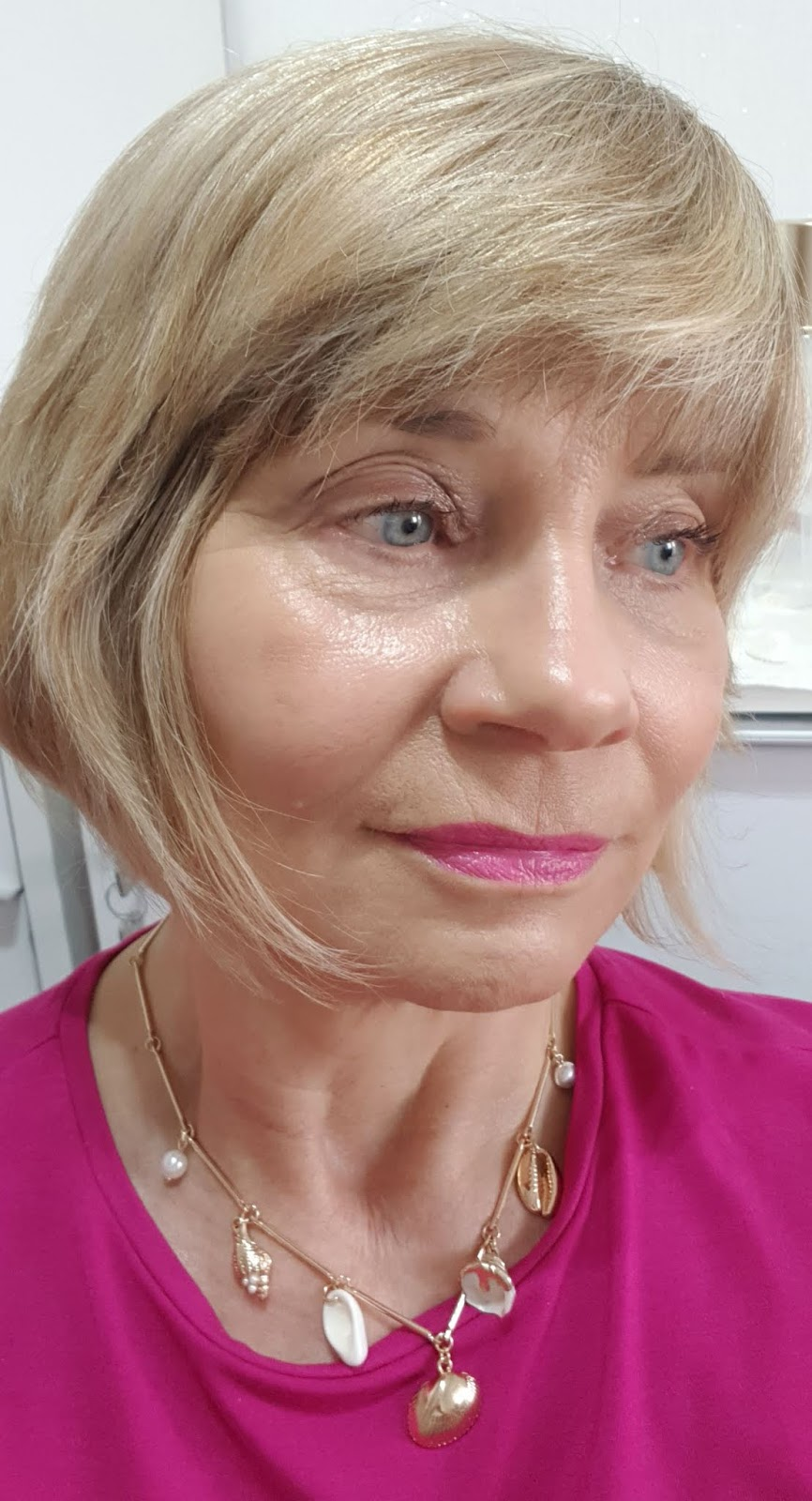Woman aged over 50 with pink top and pink lipstick