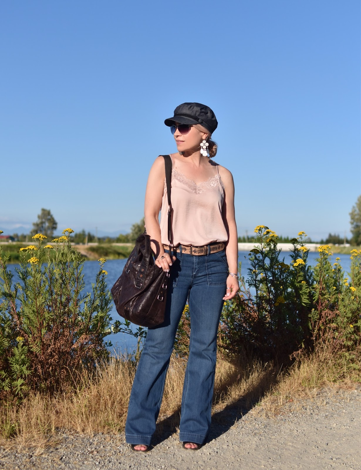 Monika Faulkner personal style inspiration - styling a pink lace-trimmed camisole with flare jeans and a baker boy cap