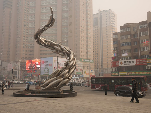 sculpture of fish swimming in a twisted upward direction on a foggy / smoggy day in Dalian, China