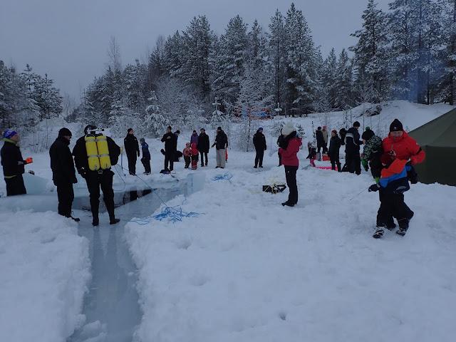 Sukeltaja ja muita ihmisiä seuraa avannon ympärillä jäällä sukellustapahtumaa