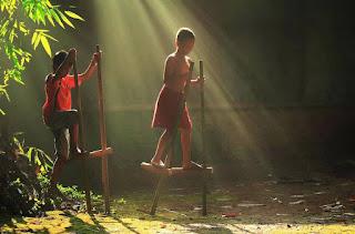 Brinquedo tradicional, geralmente fabricado pelas próprias crianças. Consiste em duas hastes de madeira que têm, cada uma, um pequeno degrau fixado a uma altura aproximada de  vinte a quarenta centímetros da extremidade inferior. Com os pés apoiados nos degraus, as mãos segura anda firmemente na parte superior da perna-de-pau, as crianças andam pelo espaço disponível, procurando equilibrar-se. Muitos fazem corridas utilizando as pernas de pau.  Descrição:Foto: Um foco de luz, formado por raios de sol, incide sobre dois meninos que brincam descalços com pernas-de-pau e clareia o chão de terra batida coberto por pequenos gravetos, folhas e pedrinhas. O menino que está a frente, equilibra-se sobre a perna de pau e avança o passo com o pé esquerdo. Ele usa apenas bermuda vermelha; o outro, logo atrás, em posição de subida, segura as duas hastes, apoia o pé direito no suporte, com o outro pé no ar; usa camiseta vermelha e bermuda jeans. Na lateral esquerda, folhagens de bambu, iluminadas pela difusão dos raios do sol.