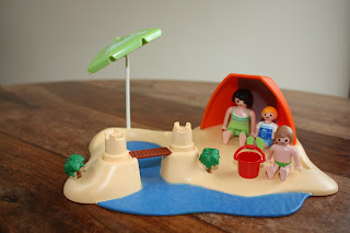 Playmobil figures by a pool and sand castles on holiday