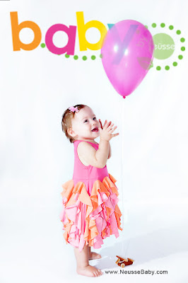 granddaughter baby girl turning one year old having portrait done with a pink balloon standing all by herself.