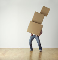 man with large stack of boxes falling over
