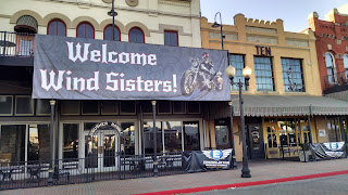 Vinyl sign on front of building: WELCOME WIND SISTERS
