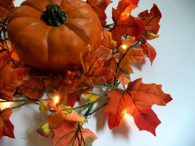 pumpkin and a leaf garland with string lights