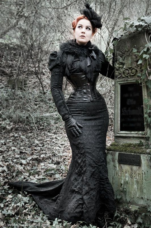 Redheaded woman by grave at cemetary wearing a neo-victorian mourning dress in black brocade fabric with underbust corset, gloves, fascinator and fur wrap.