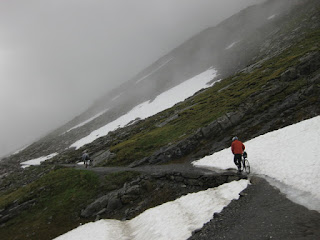 Cyclists traversing the gravel path next to snowbanks, Gemmipass, Switzerland