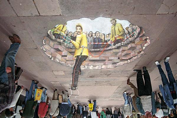 Yer yüzünden yer altına inen insanları gösteren ters kaldırım sanatı veya tavan sanatı resmi