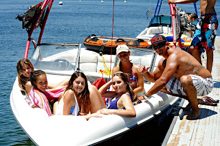 Four female teenage campers sitting in their docked speed boat while their boat driver joins them for a group photo.