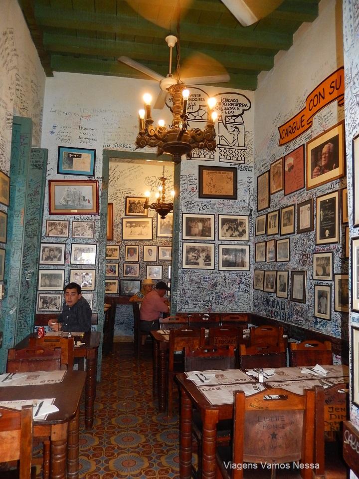 Interior do bar La Bodeguita del Medio, mesas postas e paredes desenhadas