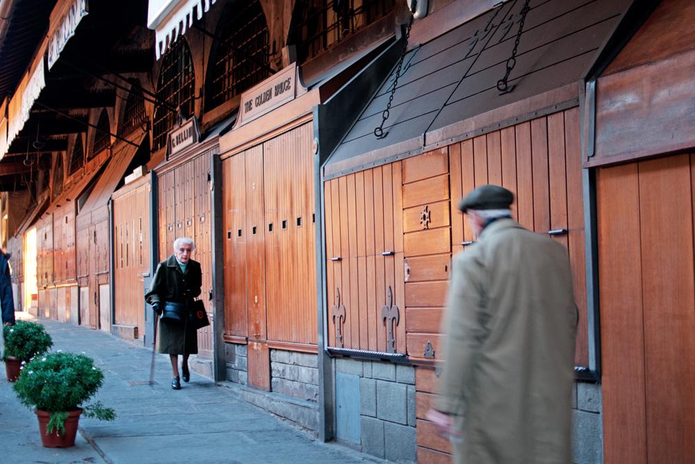 Fin de journée sur le Ponte Vecchio, les boutiques sont fermées, deux personnes le traversent