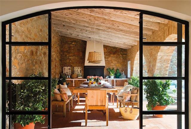 vistas del porche de piedra a traves de puertas de hierro y cristal chicanddeco