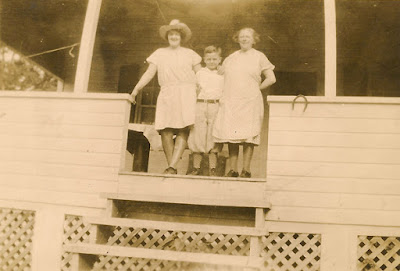 Mystery Photo! A woman in a cowboy hat, a boy, and an older woman wearing an apron, all standing on a porch. Unidentified.