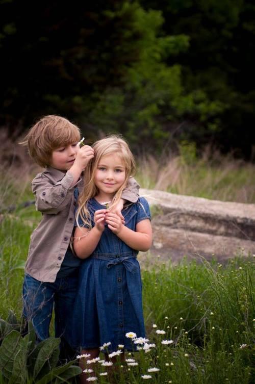 Casal de crianças, simbolizando a amizade, num campo entre flores.