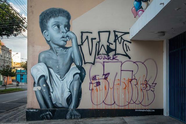 Grafite de menino de rua sentado no meio fio, na Rua Inácio Lustosa