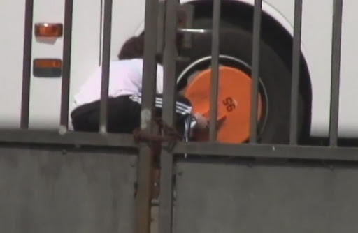 A sneaky Dutch fan is seen placing a big orange wheel-clamp on Germany's team bus