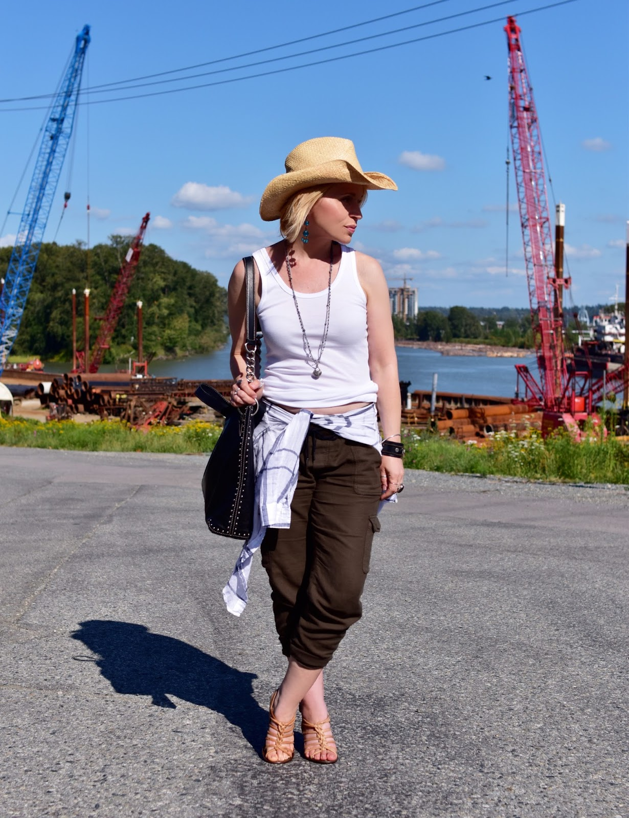Monika Faulkner styles a white boyfriend tank with slouchy cargos, strappy nude sandals, a plaid shirt, and a cowboy hat