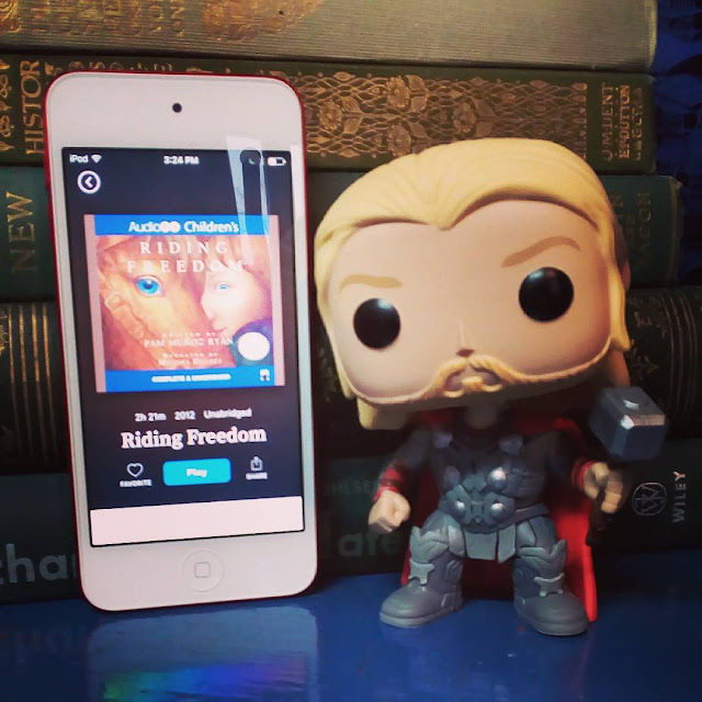 A large-headed Funko Pop bobblehead of Marvel's Thor stands next to a white iPod propped up against a stack of green vintage hardcovers. The iPod has the cover of Riding Freedom on its screen. It shows a young white person hugging a chestnut horse's head.